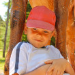 Smiling kid wearing a cap in the summer park — Stock Photo