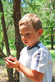 Thoughtful kid in the park holds snails — Stock Photo