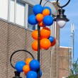 Colourful balloons adorn the column with lantern on a city stree — Stock Photo