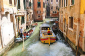 People in boats  move along a canal in Venice, Italy  — Stockfoto