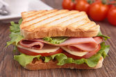 Sandwich on wood background — Stock Photo