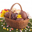 Easter egg in wicker basket with flower — Stock Photo #22284729
