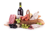Wicker basket with sausages, ham and wine — Stock Photo