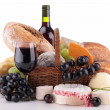 Wicker basket with bread, cheese and wine — Stock Photo