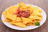 Corn tortilla chips with spicy sauce — Stock Photo
