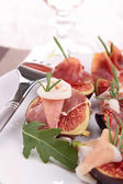 Appetizer, fig and prosciutto ham — Stock Photo