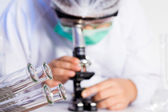 Laboratory assistant working with a microscope in lab — Stock Photo