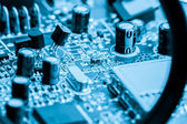 Close-up of electronic circuit board on blue background — Stock Photo