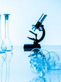 Microscopio y tubos de ensayo utilizados en laboratorio. — Foto de Stock