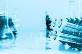 Tubos de ensaio closeup sobre fundo azul...médico produtos vidreiros — Foto Stock