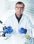 Scientist working in the lab , examines a with liquid — Stock Photo