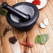 Tree spoons with spices and bundle of herbs, mortar and pestle — Stock Photo #39235945