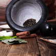 Tree spoons with spices and bundle of herbs, mortar and pestle — Stock Photo #39236793
