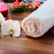 Wellness and spconcept with candles, collection of towels and part of massage table. — Stock Photo #41016211