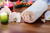 Wellness and spa concept with candles, collection of towels and part of massage table. — Stock Photo