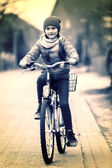 Cute smiling little girl with bicycle on road. — Stock Photo