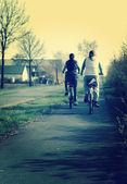 Girls riding bikes .Retro image — Stockfoto