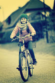 Little girl with bicycle on road.Retro image — Stock Photo