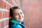 Portrait of   little cute girl next to Brick Wall — Stock Photo