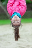 Little Girl Hanging Upside-down on a playground — Stock Photo