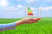 Hands holding  house with energy efficiency rating — Stok fotoğraf