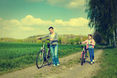 Young girl with mother on bikes  in the countryside. — Stock Photo