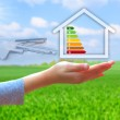 Hands holding house with energy efficiency rating — Stock Photo #48807119