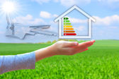 Hands holding house with energy efficiency rating — Stock Photo