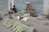 An aged man and a child prepare brooms to earn their livelihood for support their families — Stock Photo
