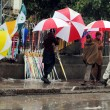 Stock Photo: Msells umbrellas to earn his livelihood for support his family, during downpour of winter season
