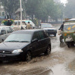 Stock Photo: Commuters pass through Mall road during downpour of winter season