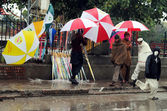 Man sells umbrellas to earn his livelihood for support his family, during downpour of winter season — Stock Photo