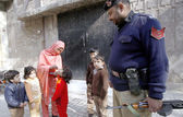 A health worker administrates polio-vaccine drops to a child during anti-polio campaign while police official stands alert to guard — Stock Photo