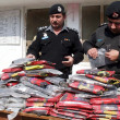 Stock Photo: Police officials inspect recovered packets of drug (Charas), which were seized during snap checking at Jamrud road