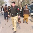 Security officials inspect the site after bombs explosions at Political Agent Khyber office in Peshawar - Stock Photo