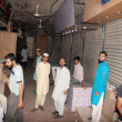Постер, плакат: Shops keepers gather in market after robbery in several shops at Bazar e Faisal at Karimabad area in Karachi