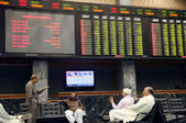 Stockbrokers sit near an index board showing a sharp rise in stocks during trading session at Karachi Stock Exchange — Stock Photo