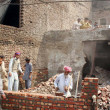 Stock Photo: Laborers busy reconstruction of ransacked houses that set to fire by angry mob during protest against blasphemy committed by ChristimSawMasih