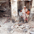 Woman of Christian Community sits worried along with her children at their demolished house by an angry mob during protest against blasphemy committed by a Christian man Sawan Masih — Stock Photo