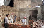 Laborers busy reconstruction of ransacked houses that set to the fire by an angry mob during protest against blasphemy committed by a Christian man Sawan Masih — Stock Photo