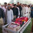 Stock Photo: Gather near coffin of PolicemGul Sher, who was gunned down by unidentified persons