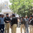 Stock Photo: Police officials and gather at site after bomb explosion at Landhi arein Karachi