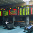 Pakistani traders sit beneath an electronic screen at the Karachi Stock Exchange (KSE) premises — ストック写真