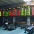 Pakistani traders sit beneath an electronic screen at the Karachi Stock Exchange (KSE) premises — Stockfoto