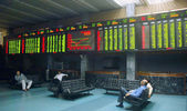 Pakistani traders sit beneath an electronic screen at the Karachi Stock Exchange (KSE) premises — Stock Photo