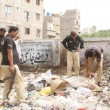 Police officials inspecting a tortured sack pack body that found near Old Sazbi Mandi from a garbage dump, in Karachi  — Stock Photo