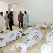 Stock Photo: People gather near dead bodies of passengers, who killed unknown armed assailants at Giyani Pul near Mach arein BolDistrict, at local hospital in Quetta