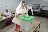 Voters cast their votes at a polling station during by-election for NA-01 in Peshawar — Photo