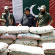 Stock Photo: Security officials inspect recovered 6000 kg packets of drug (Charas), which were seized during snap checking at check-post