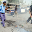 Security officials removing burning tyres from road that torched by ChristiCommunity as they were protesting against dual suicidal bomb blast attack on church of Kohati gate, — Stock Photo #31960037